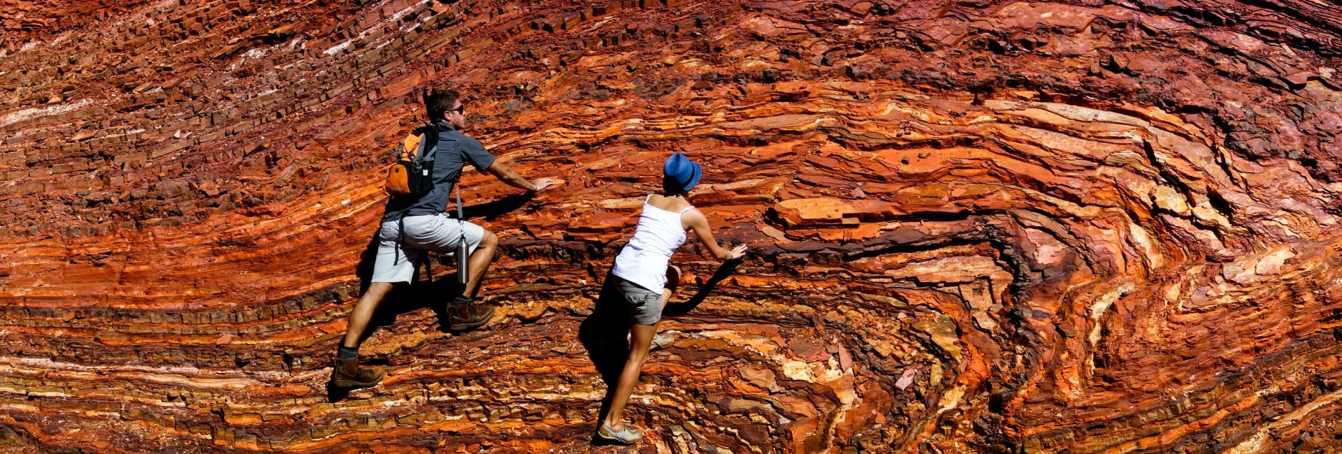 Couple climbing rock wall in Karijini National Park.